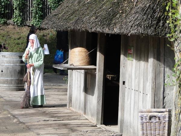 Een vrouw uit de late middeleeuwen veegt haar stoep in het Archeon